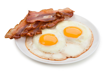 Plate with fried eggs, bacon isolated on white background